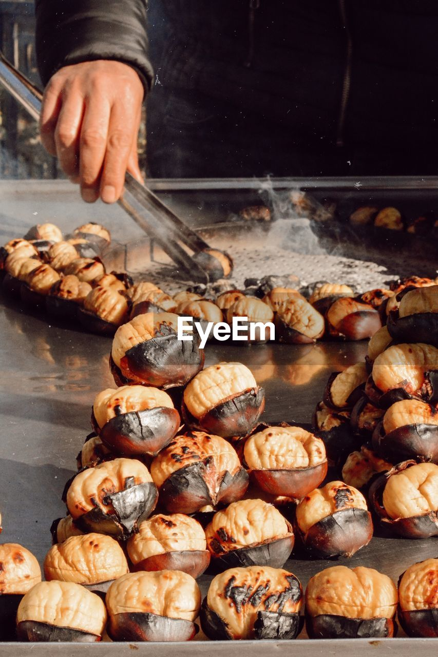 food and drink, food, freshness, preparation, human hand, hand, one person, human body part, preparing food, barbecue, heat - temperature, day, barbecue grill, close-up, indoors, grilled, occupation, large group of objects, holding, finger