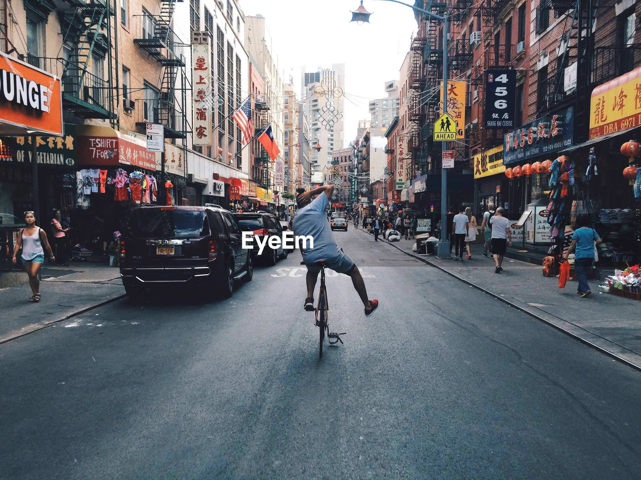 Rear view of man cycling in chinatown