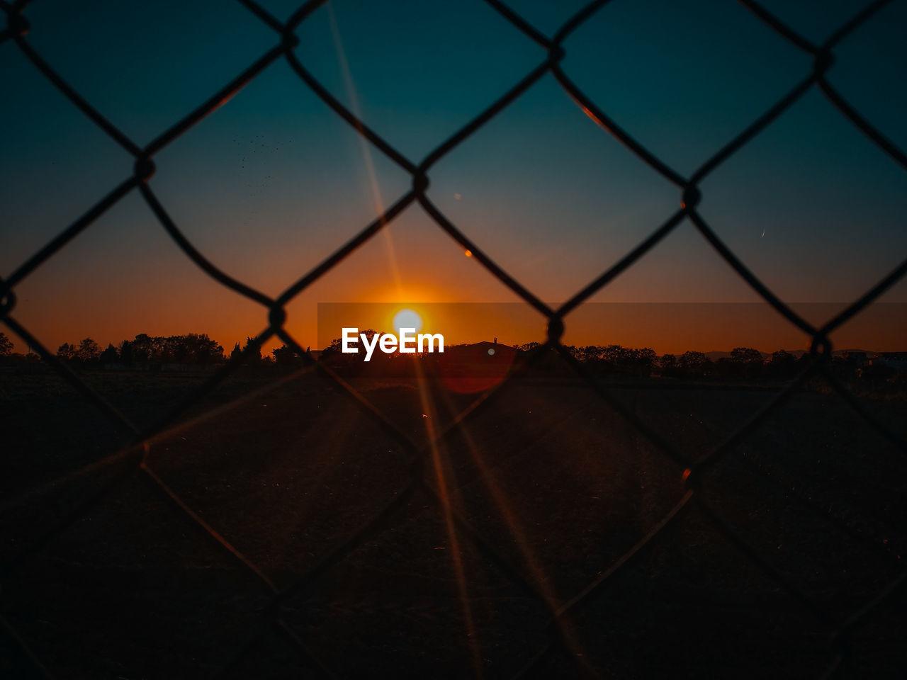 Sun Seen Through Chainlink Fence