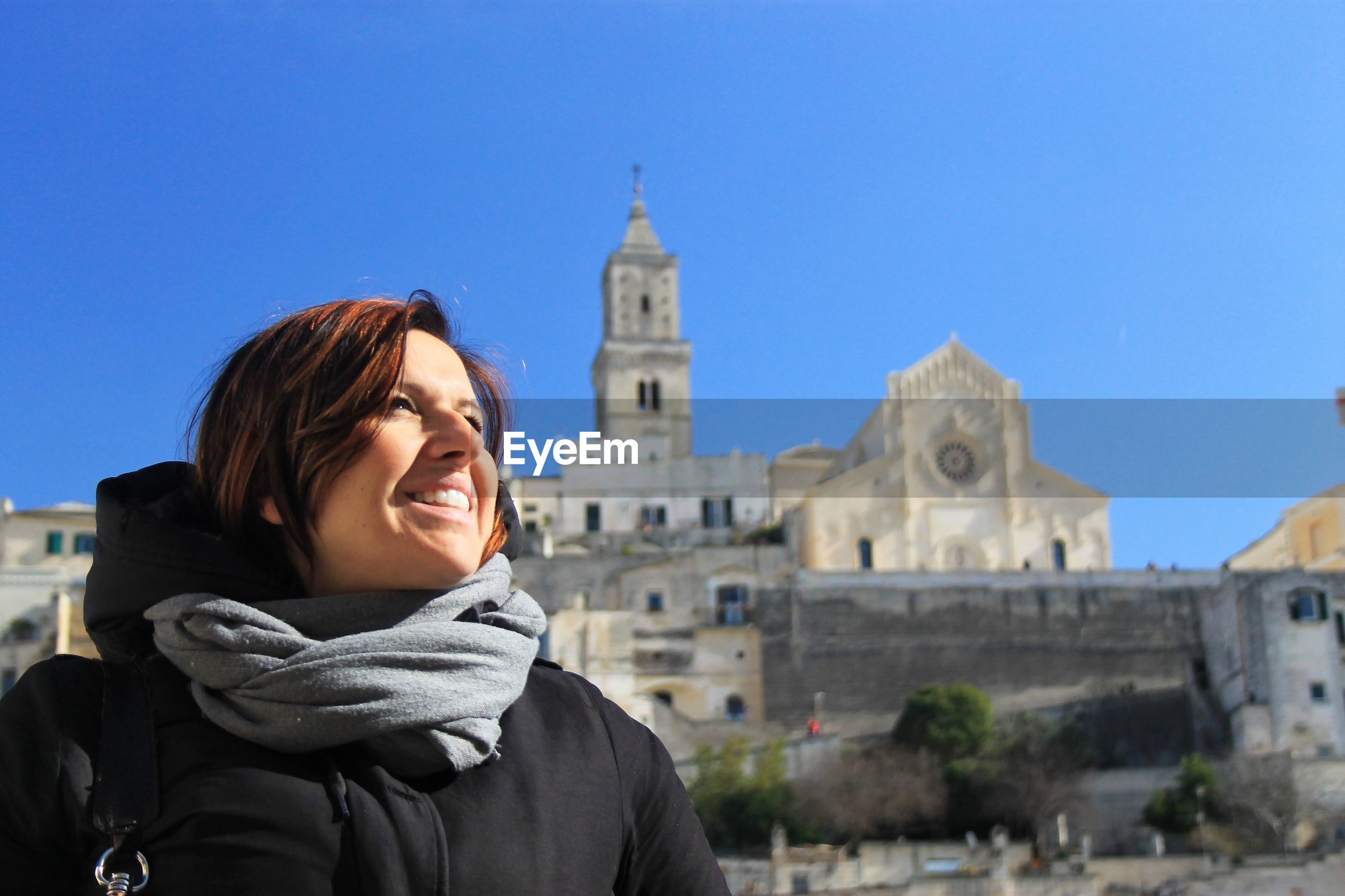 Smiling woman standing against church
