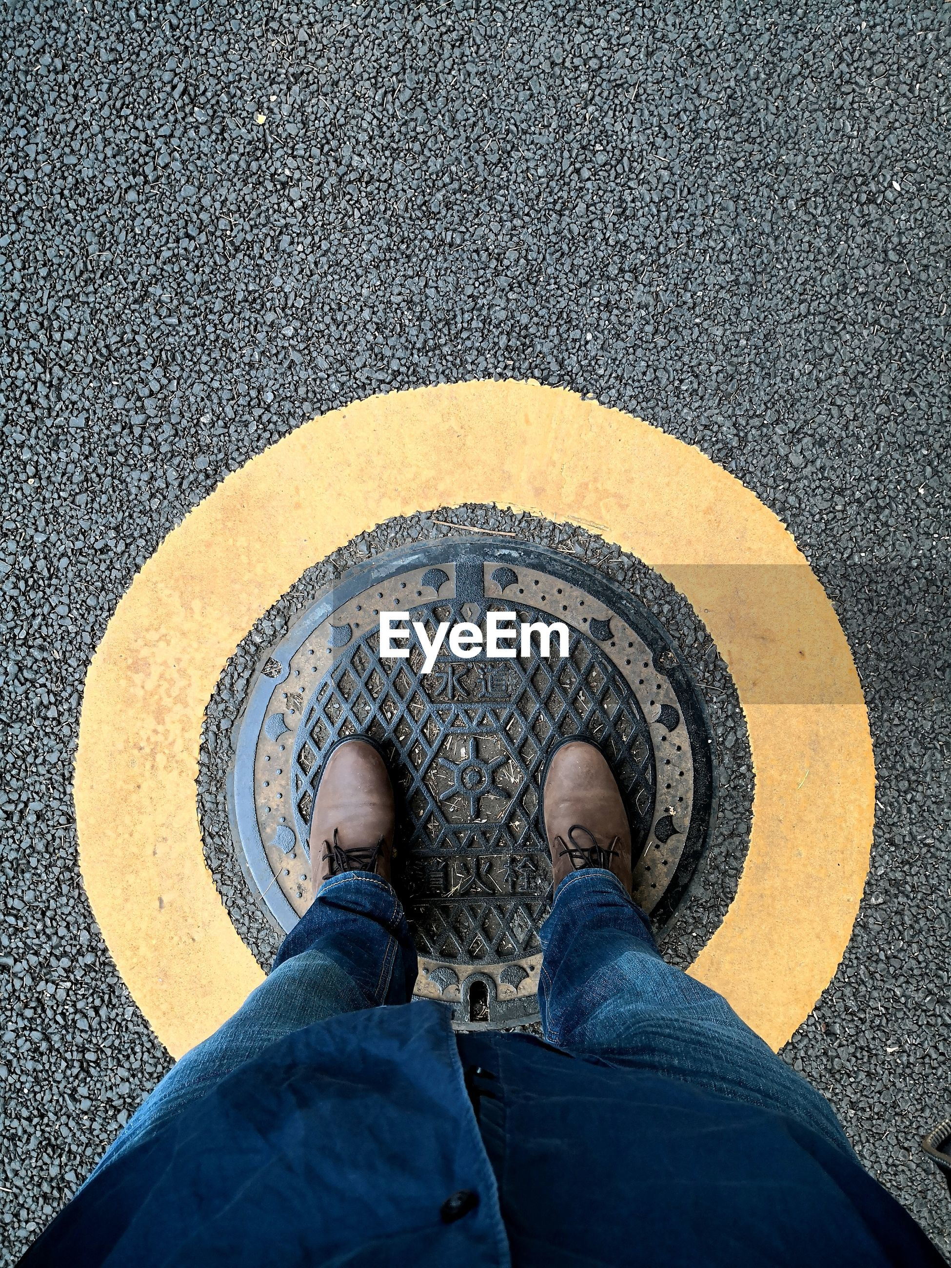 Low section of man standing on manhole