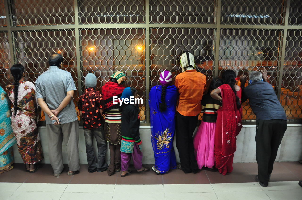 Rear view of people looking through window in airport