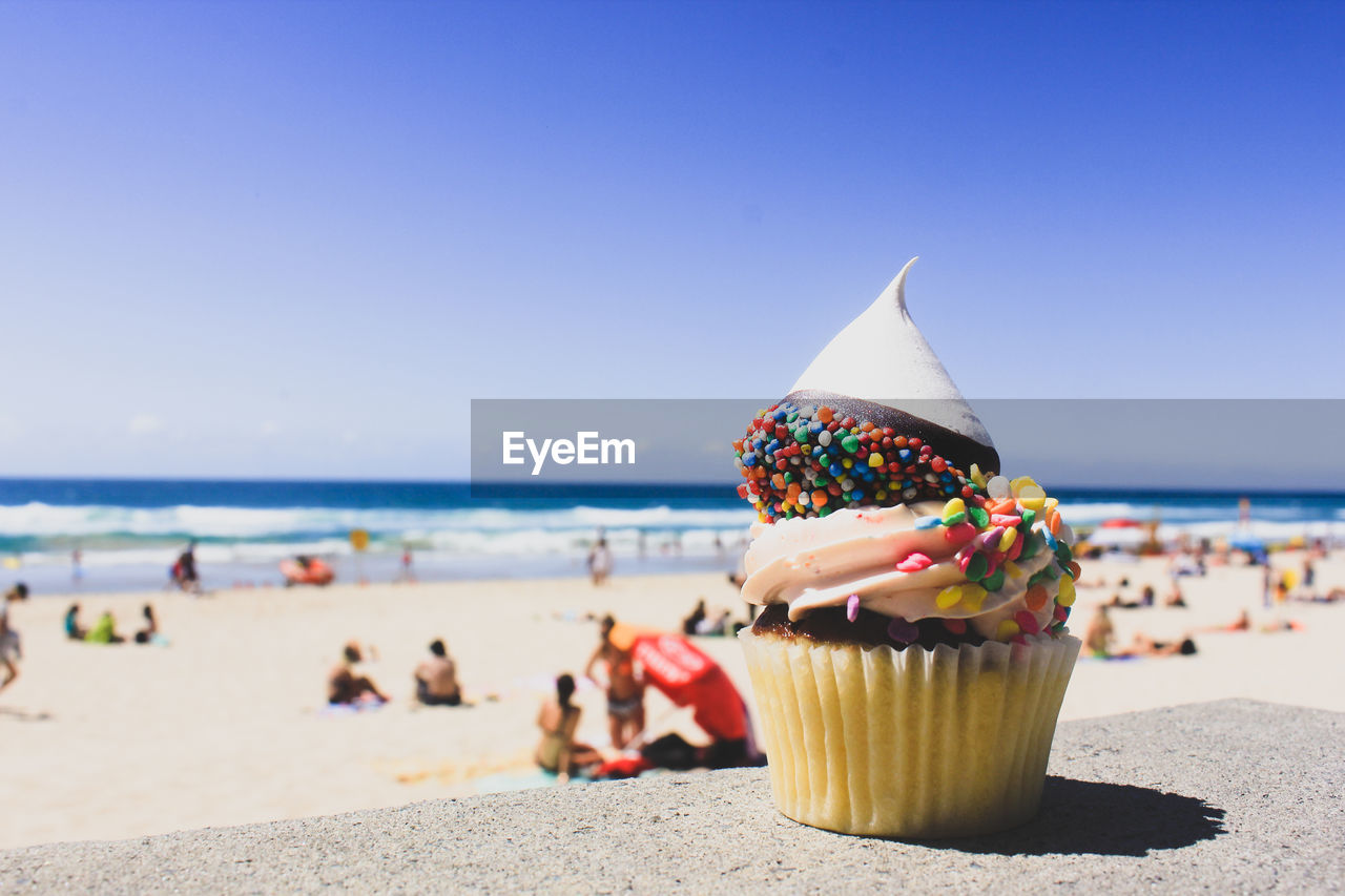 Close-Up Of Cupcake On Beach Against Clear Blue Sky