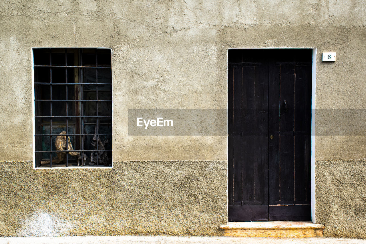 architecture, built structure, building exterior, window, building, day, no people, entrance, closed, outdoors, mammal, door, protection, residential district, sunlight, vertebrate, security, animal themes, animal, wall, window frame