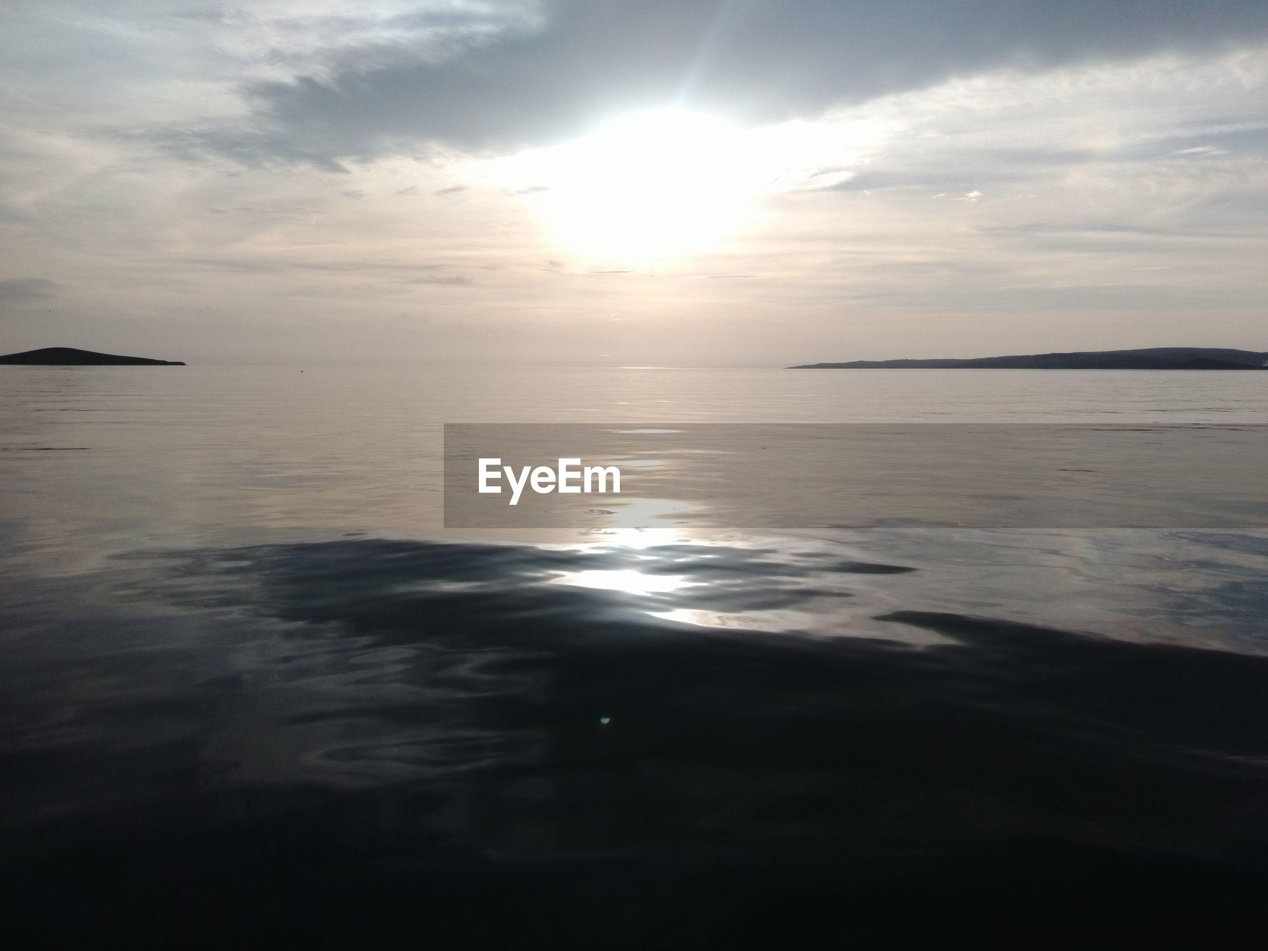 water, sea, tranquil scene, sky, reflection, scenics, tranquility, sun, beauty in nature, horizon over water, sunset, nature, waterfront, sunlight, cloud - sky, idyllic, sunbeam, rippled, cloud, seascape