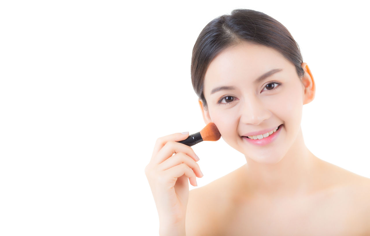 Portrait of smiling young woman applying beauty product with brush against white background