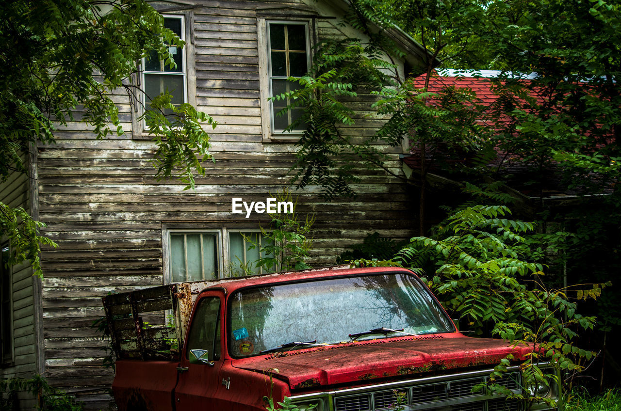 built structure, architecture, building exterior, mode of transportation, plant, transportation, building, motor vehicle, tree, car, day, land vehicle, house, no people, nature, old, abandoned, window, outdoors, obsolete, ruined, garage