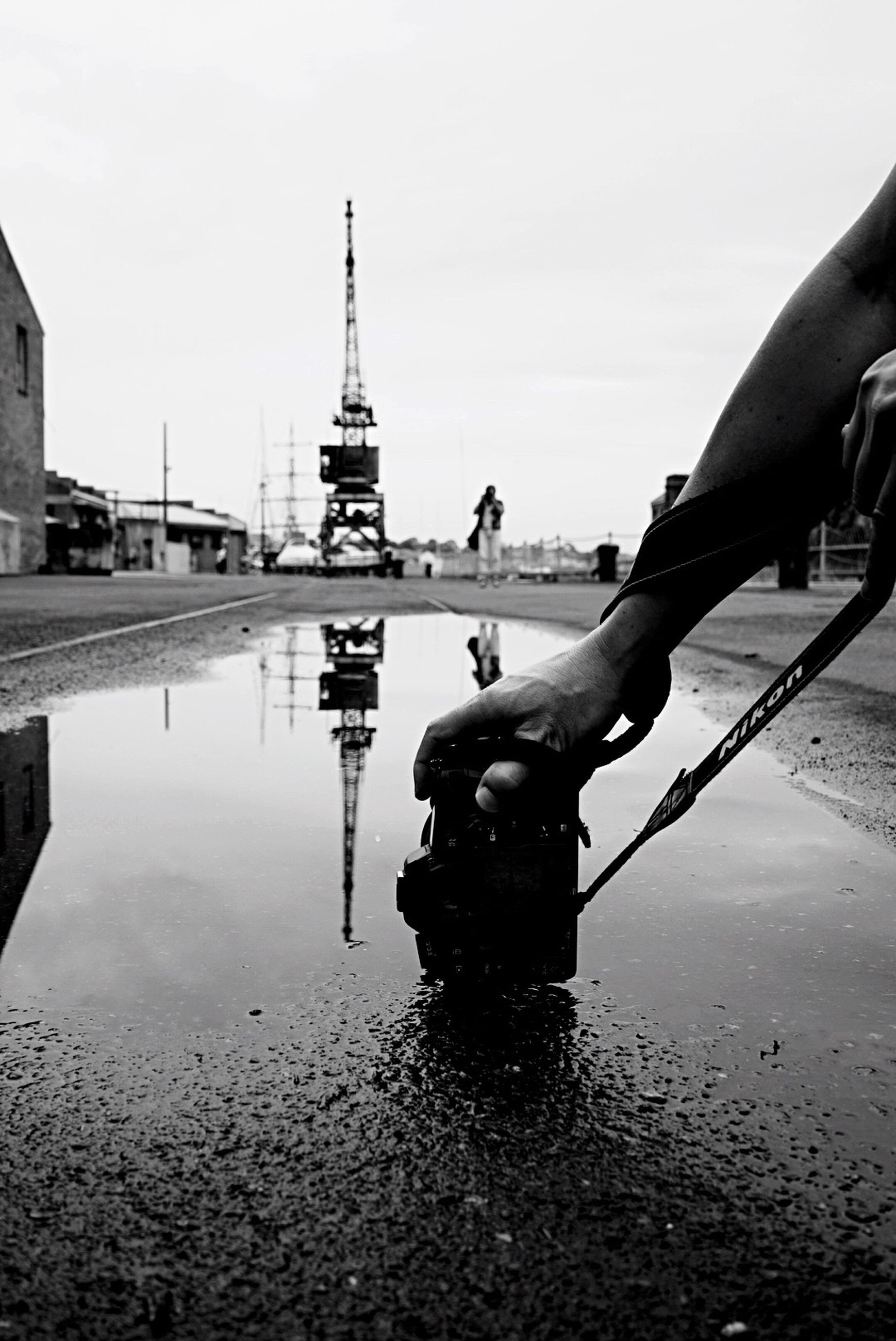 Cropped image of hand holding camera by puddle on street