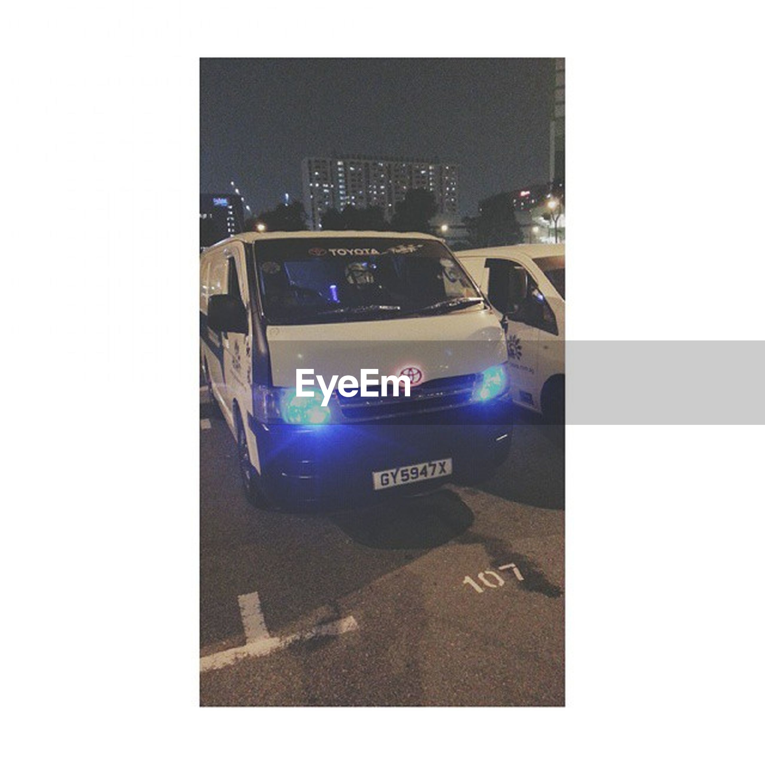 transfer print, transportation, auto post production filter, car, city, text, communication, building exterior, land vehicle, western script, street, clear sky, road, architecture, built structure, mode of transport, high angle view, illuminated, traffic, copy space