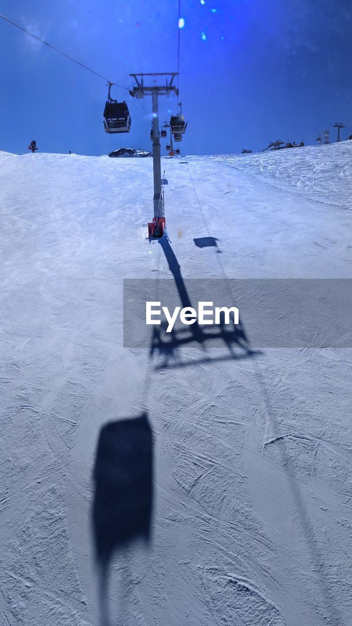 snow, cold temperature, winter, cable car, covering, nature, winter sport, ski lift, mountain, white color, day, land, shadow, transportation, sky, skiing, field, overhead cable car, scenics - nature, outdoors, snowcapped mountain, ski resort