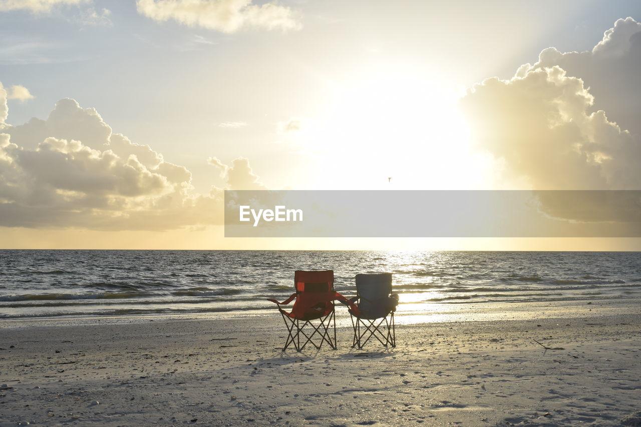 sky, horizon over water, water, sea, horizon, beauty in nature, beach, land, scenics - nature, tranquility, tranquil scene, cloud - sky, nature, chair, seat, sand, idyllic, sunlight, sunset, outdoors