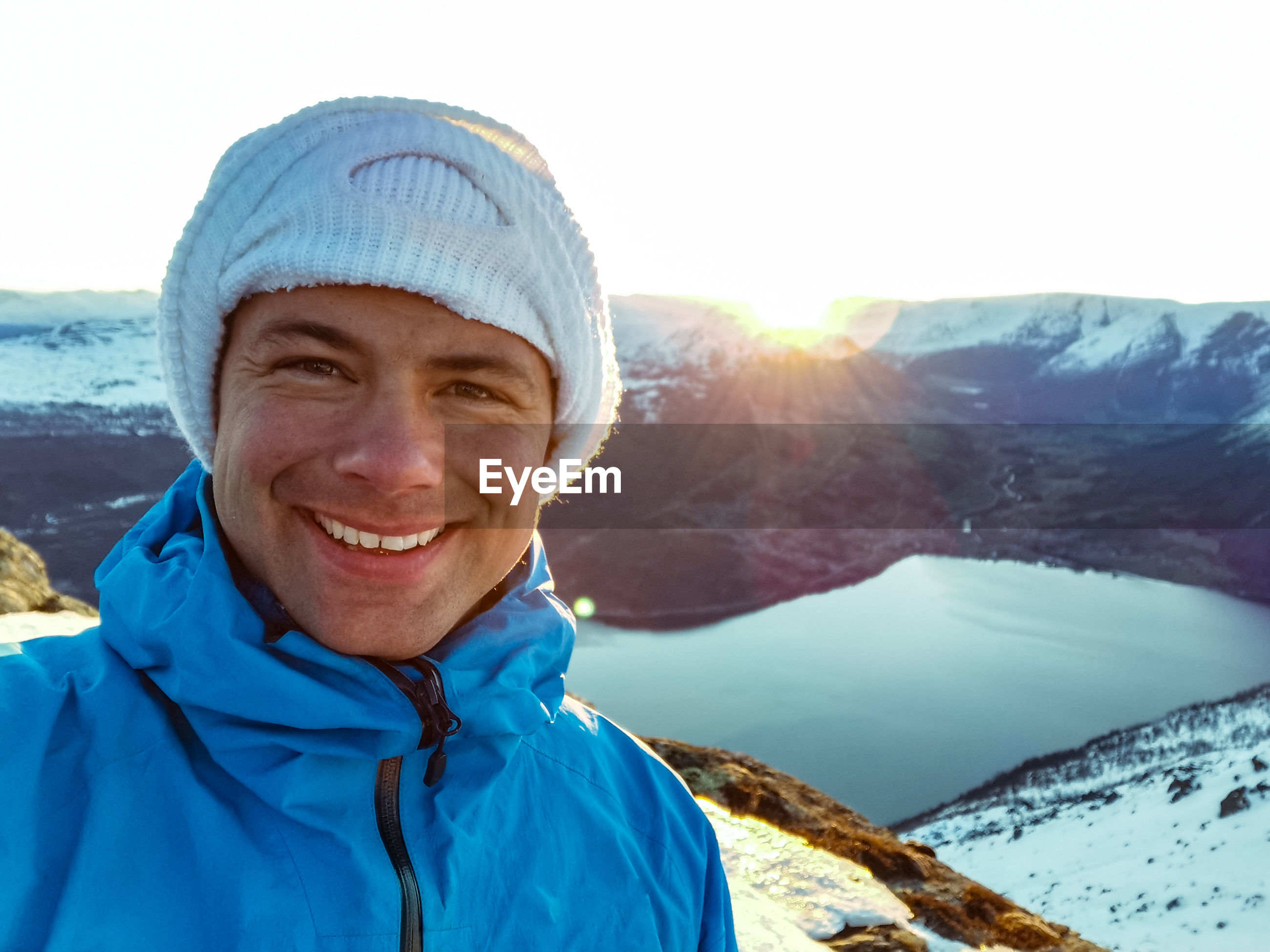Portrait of smiling man on snowcapped mountain