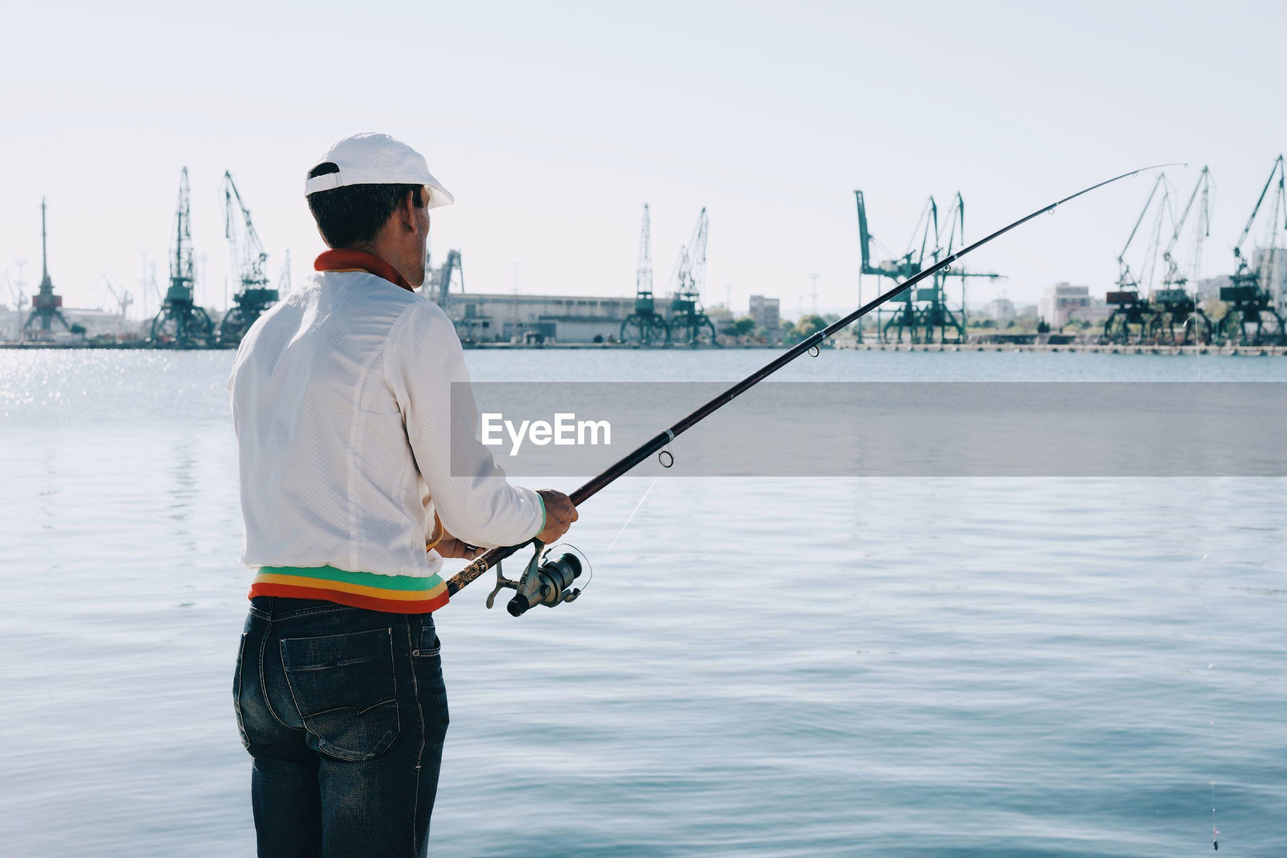 Rear view of man fishing at harbor