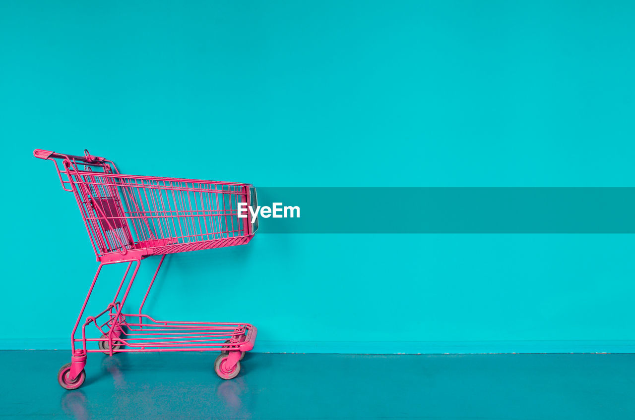 Pink Shopping Cart Against Turquoise Wall