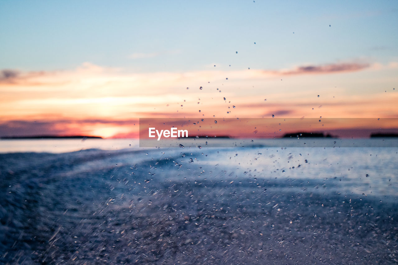 Close-up of water drops on sea against sky during sunset
