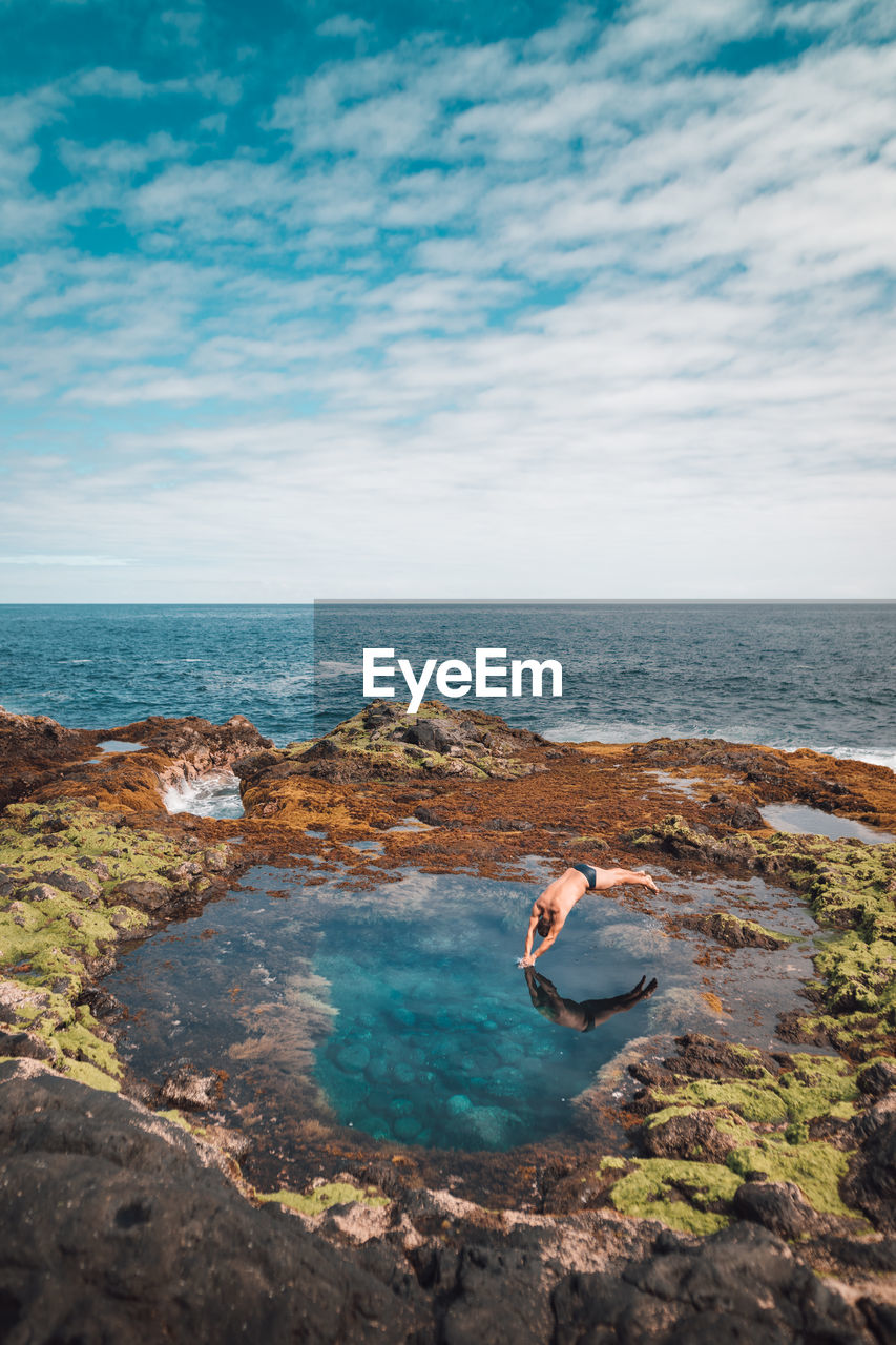 Shirtless man diving in sea against sky