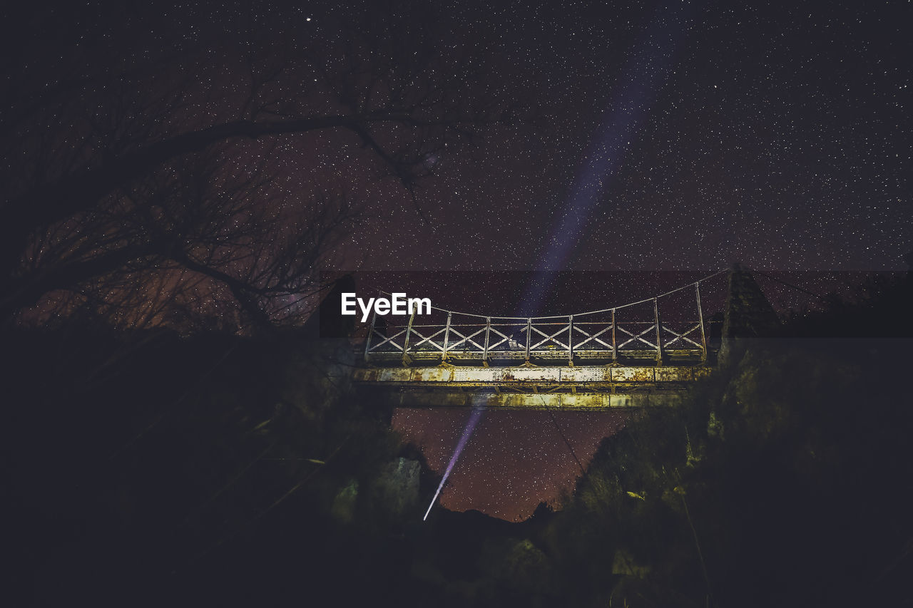 Low angle view of footbridge against sky during night
