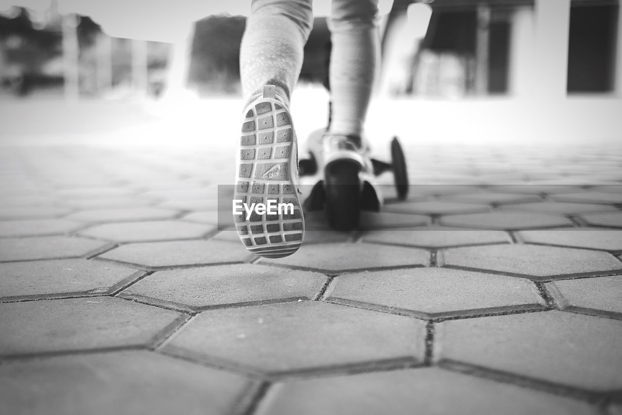 low section, human leg, real people, human body part, cobblestone, childhood, day, playing, outdoors, lifestyles, close-up, people