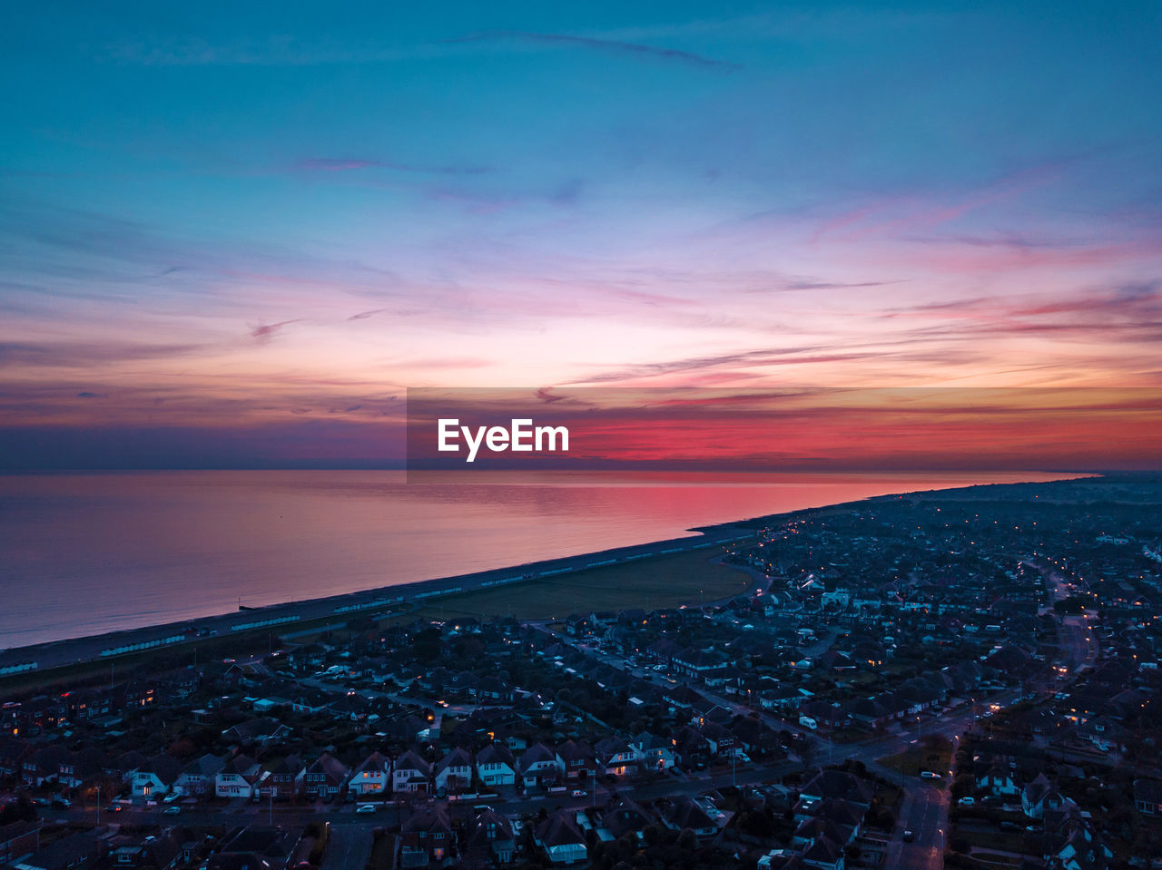 sky, sunset, cloud - sky, architecture, city, scenics - nature, building exterior, water, built structure, sea, nature, beauty in nature, cityscape, high angle view, orange color, crowd, horizon, beach, crowded, horizon over water, outdoors
