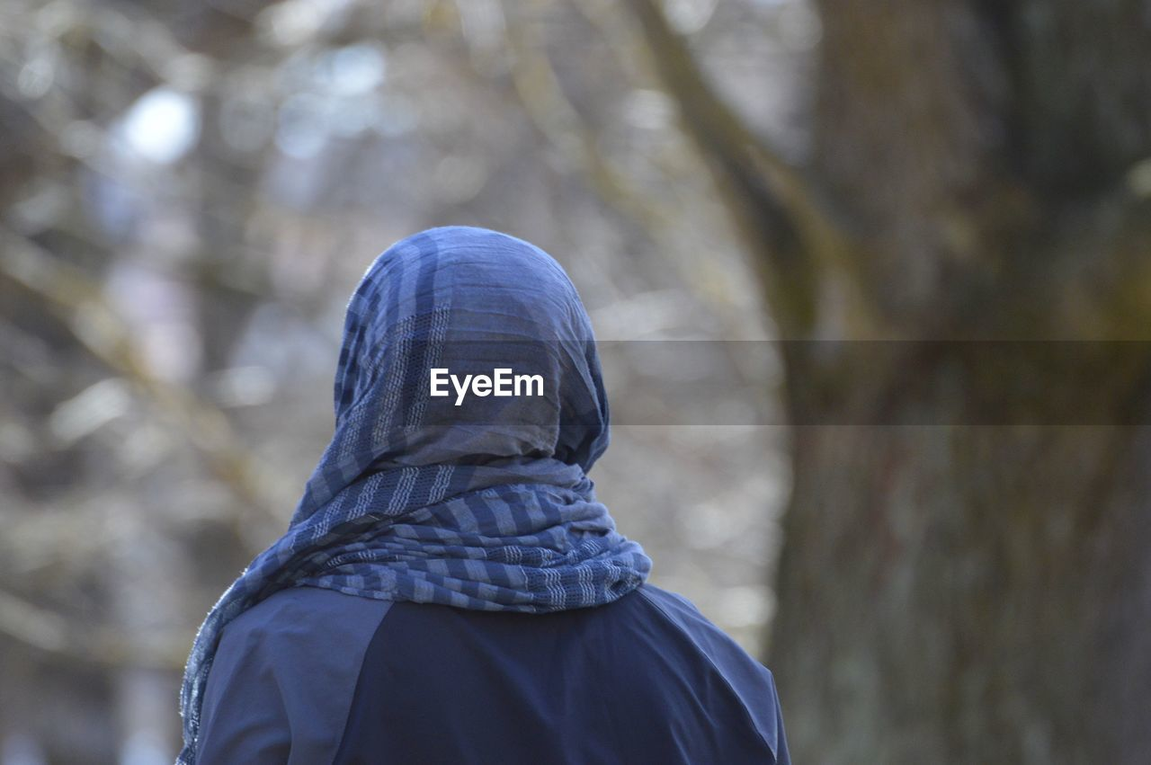 Rear view of person wearing scarf in forest
