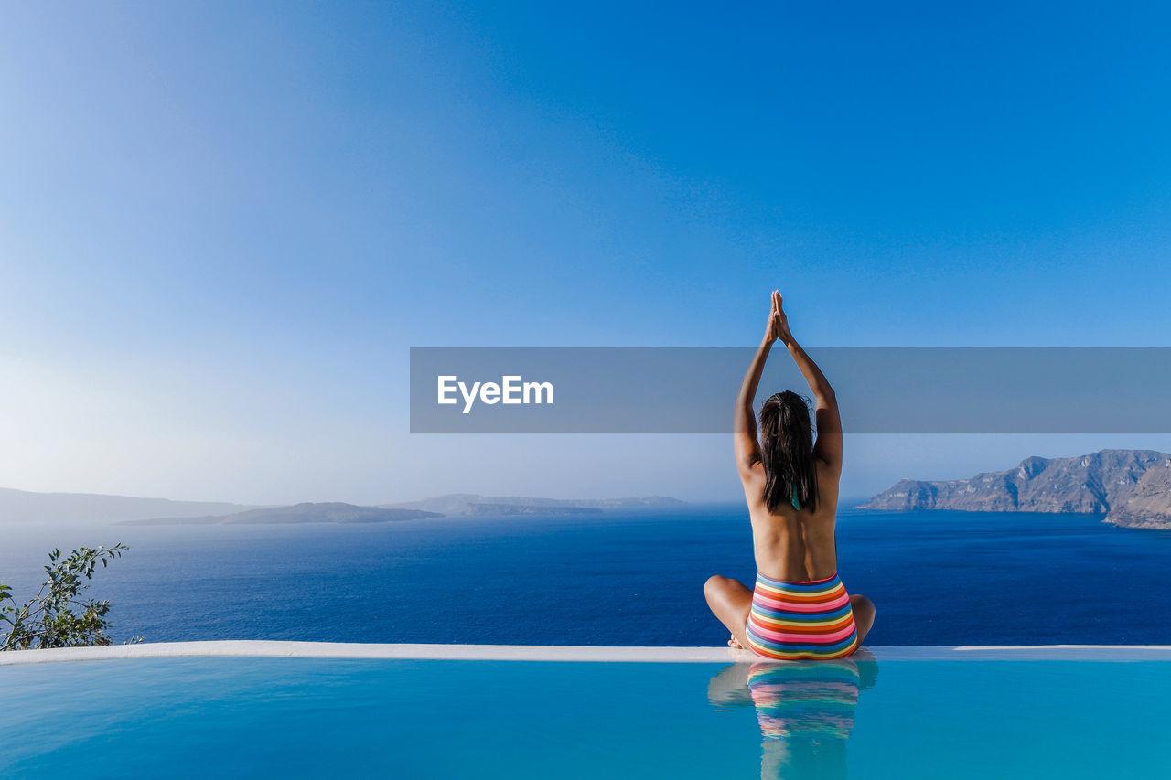Woman practicing yoga in swimming pool against sea