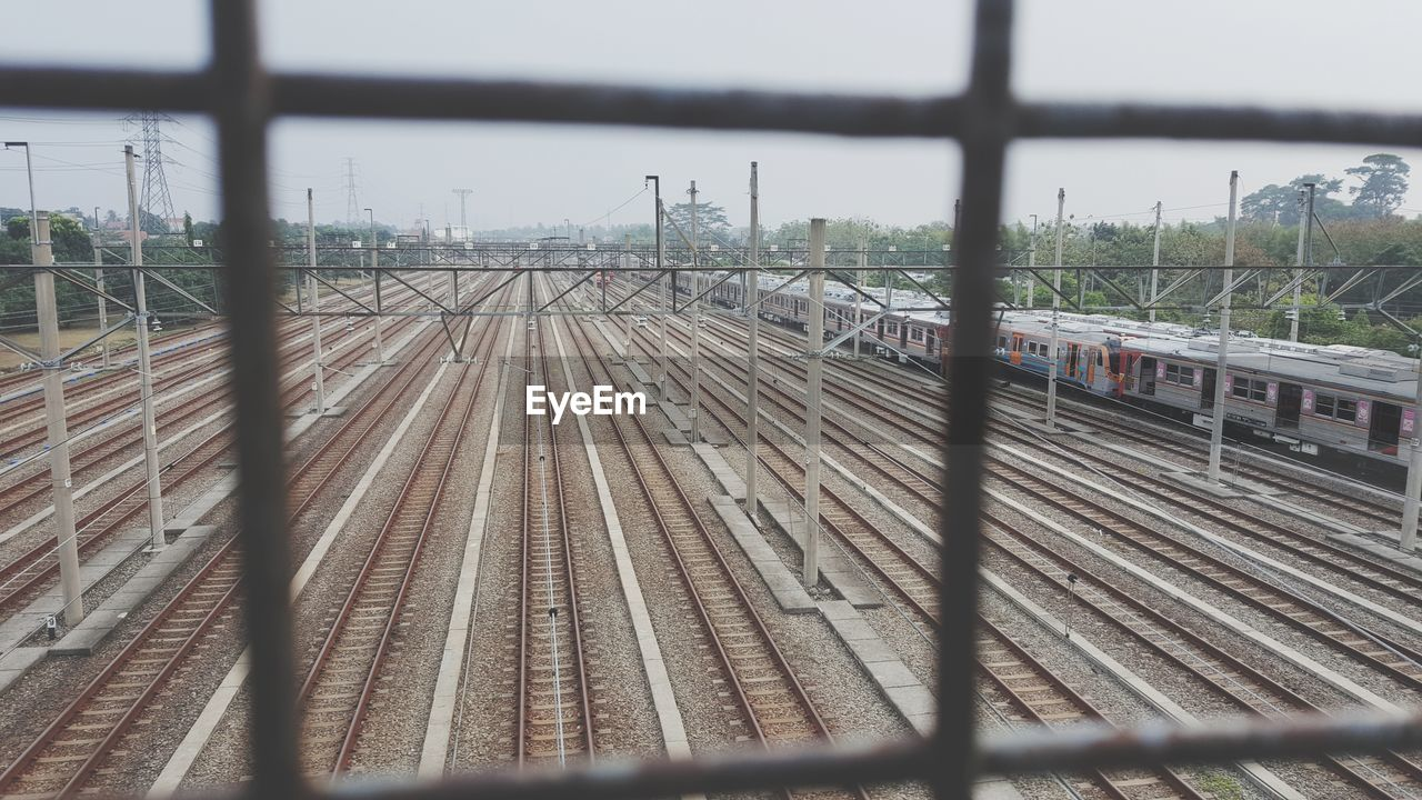 rail transportation, track, railroad track, transportation, public transportation, train, train - vehicle, mode of transportation, focus on background, sky, no people, day, metal, nature, travel, connection, outdoors, railroad station, fence, selective focus