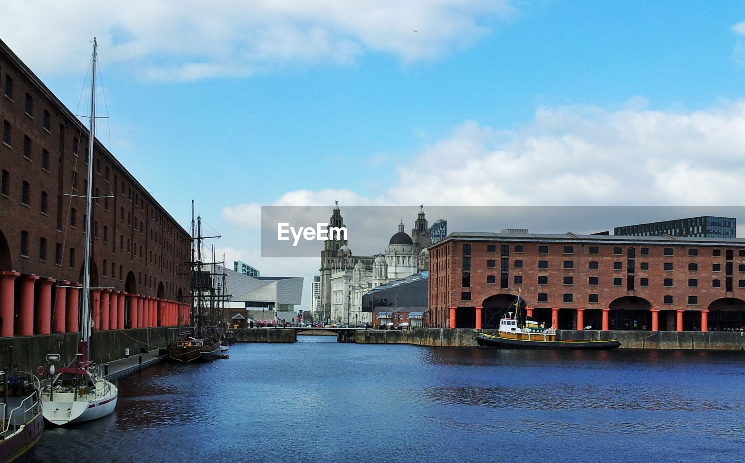 architecture, building exterior, built structure, water, sky, waterfront, canal, cloud - sky, city, transportation, cloud, mode of transport, incidental people, building, nautical vessel, river, residential building, travel destinations, residential structure, travel