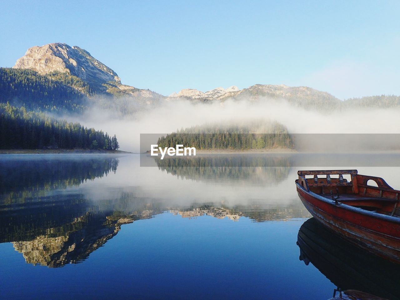 Scenic View Of Boat In Lake With Reflection During Foggy Weather
