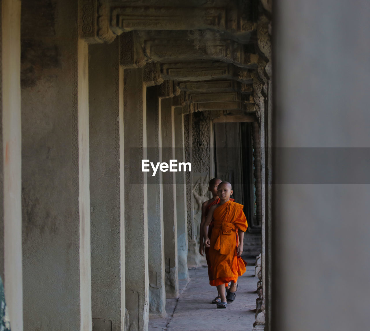 Monks Walking In Corridor Of Temple