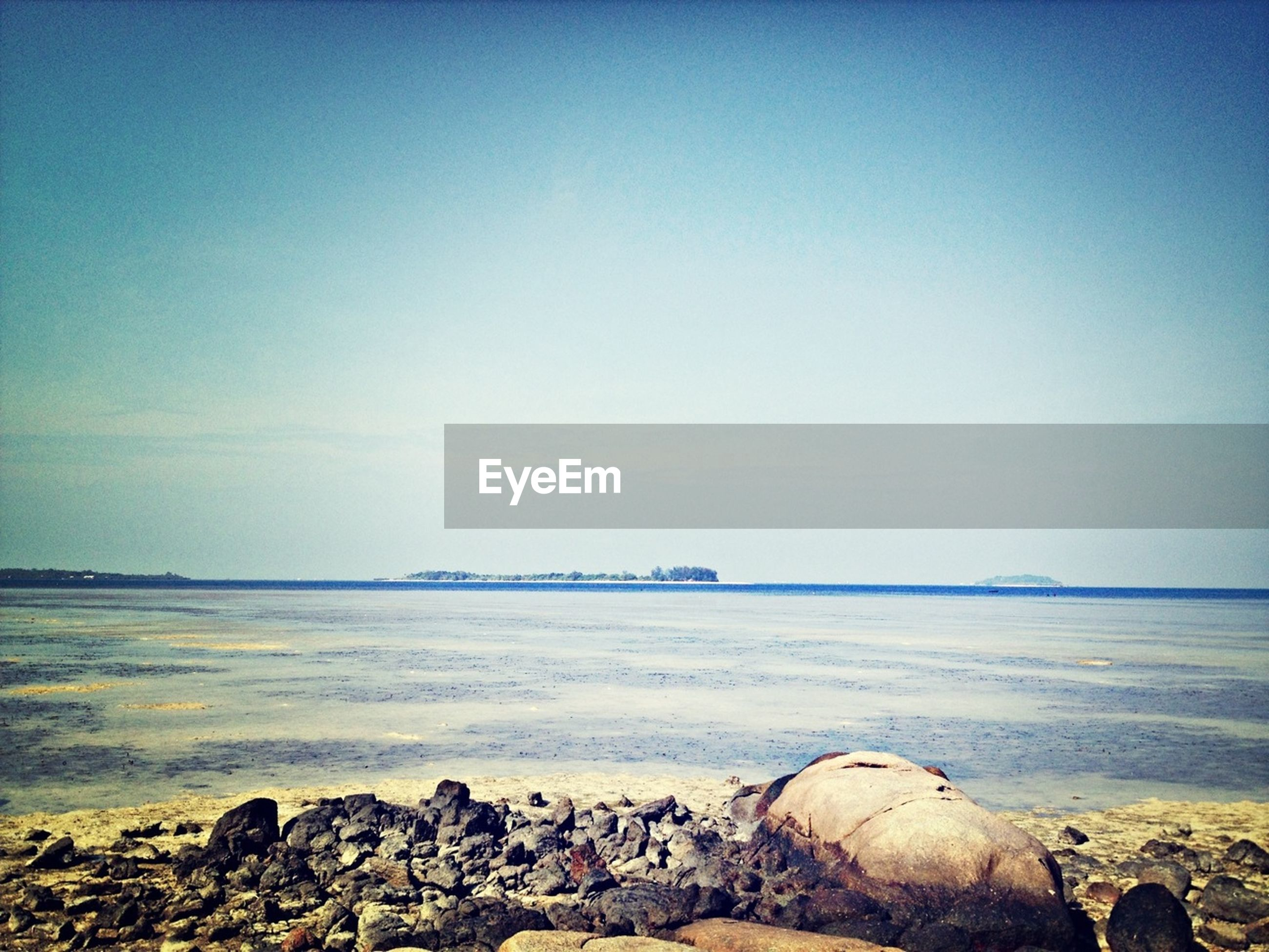 sea, water, rock - object, horizon over water, tranquil scene, beach, shore, scenics, tranquility, beauty in nature, clear sky, nature, rock, copy space, stone - object, rock formation, sky, idyllic, blue, pebble