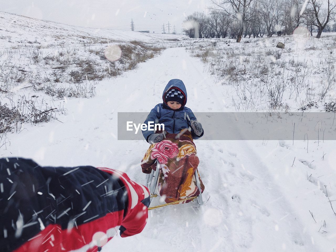 Boy sitting on sled during winter
