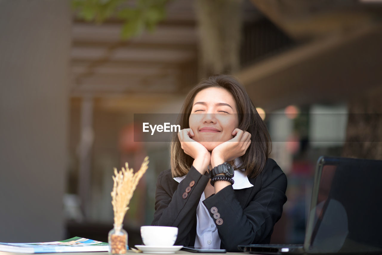 Smiling young woman with eyes closed sitting at restaurant