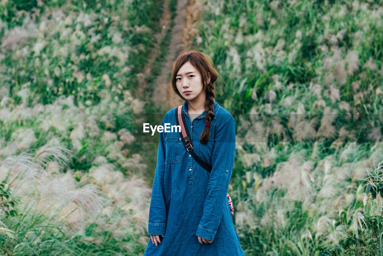 one person, young adult, young women, casual clothing, three quarter length, real people, standing, plant, front view, leisure activity, day, focus on foreground, land, looking at camera, portrait, lifestyles, hairstyle, nature, hair, beautiful woman, contemplation, outdoors, teenager