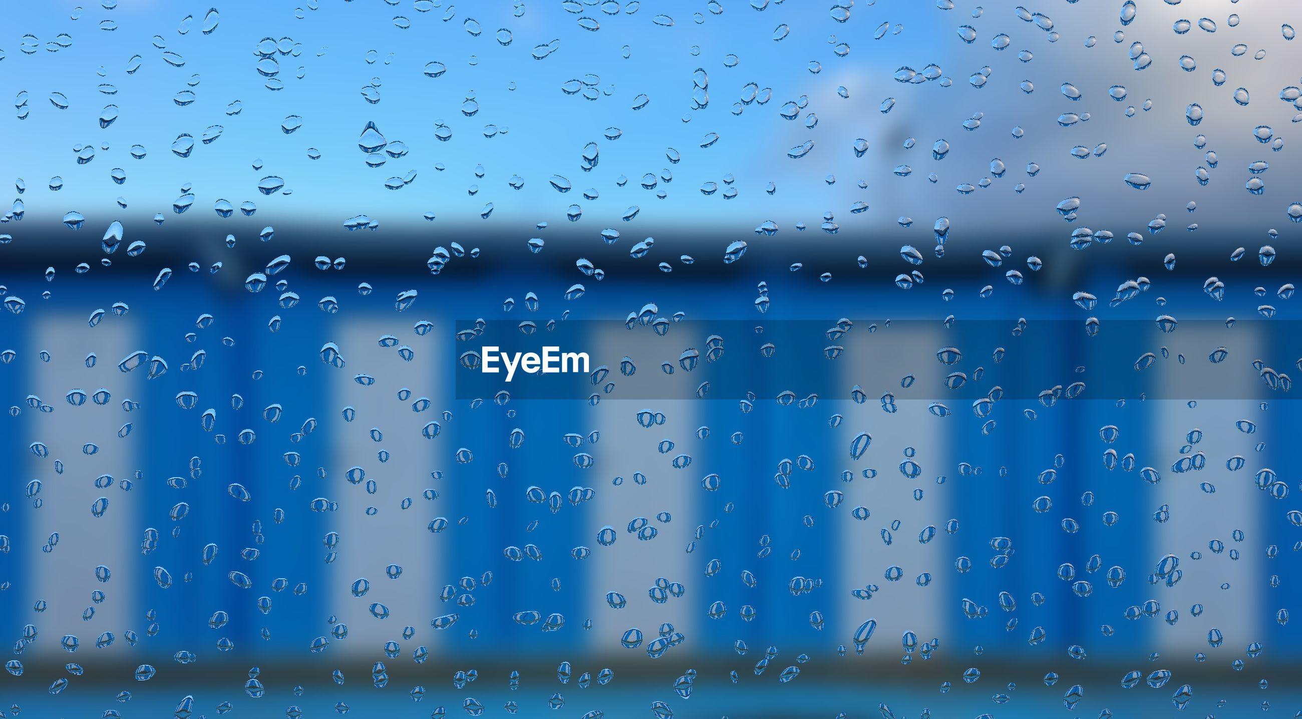 FULL FRAME SHOT OF WET GLASS WINDOW IN RAIN