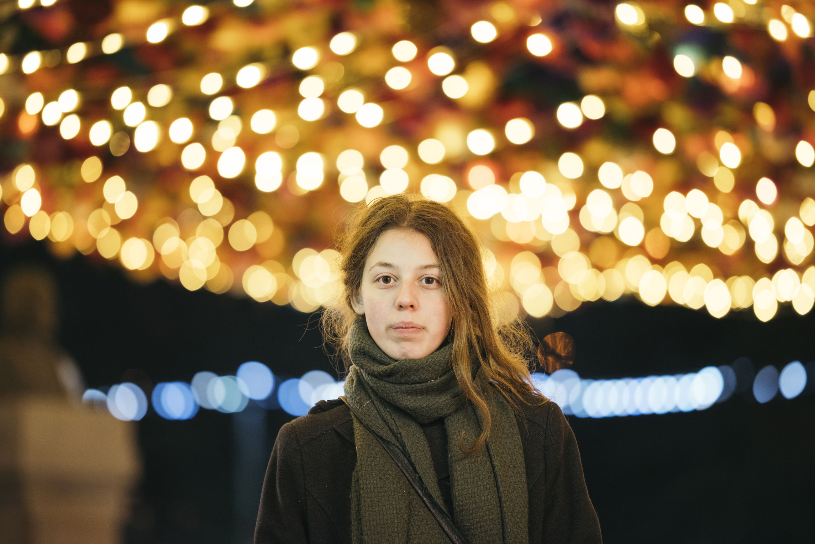 Portrait of young woman standing in illuminated park