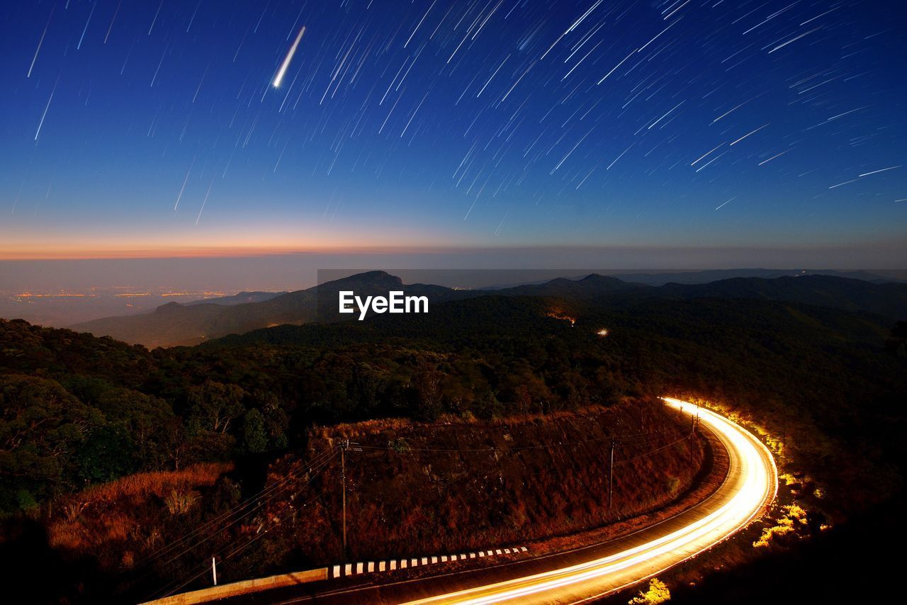 Illuminated Country Road Amidst Mountain Against Shooting Stars During Night