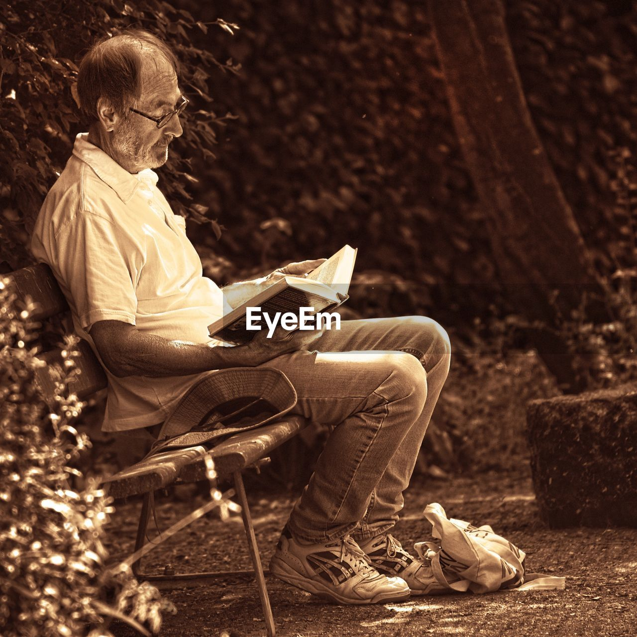 MIDSECTION OF MAN SITTING ON BOOK WITH SEAT