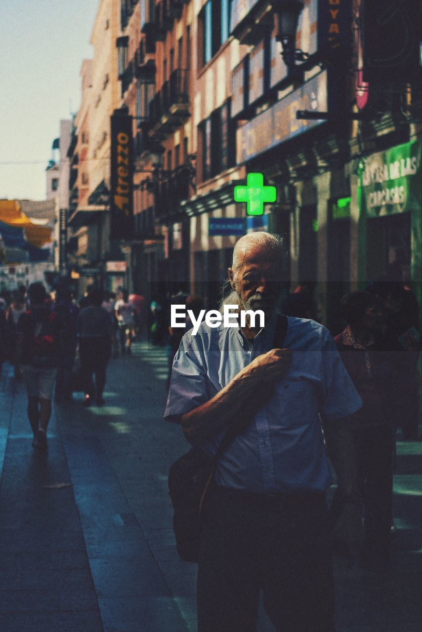 city, architecture, building exterior, street, one person, built structure, city life, real people, men, lifestyles, three quarter length, incidental people, males, adult, standing, looking at camera, night, focus on foreground, senior adult, mature men