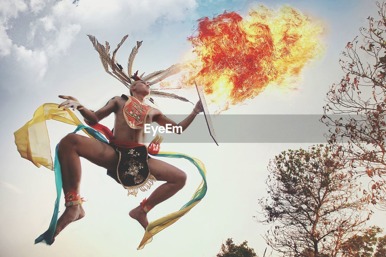 Low Angle View Of Man Wearing Traditional Clothing Blowing Fire Against Sky
