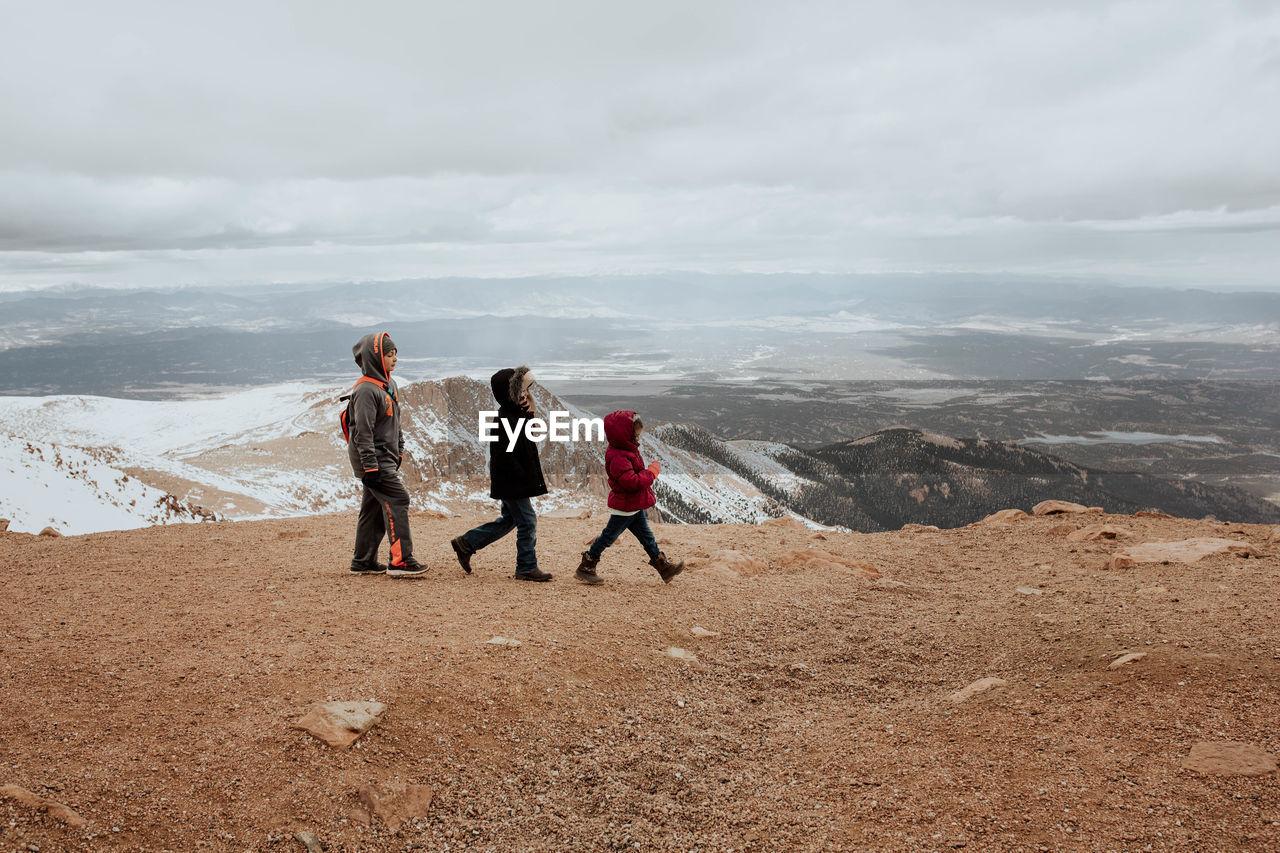 FULL LENGTH OF WOMEN ON MOUNTAIN AGAINST SKY