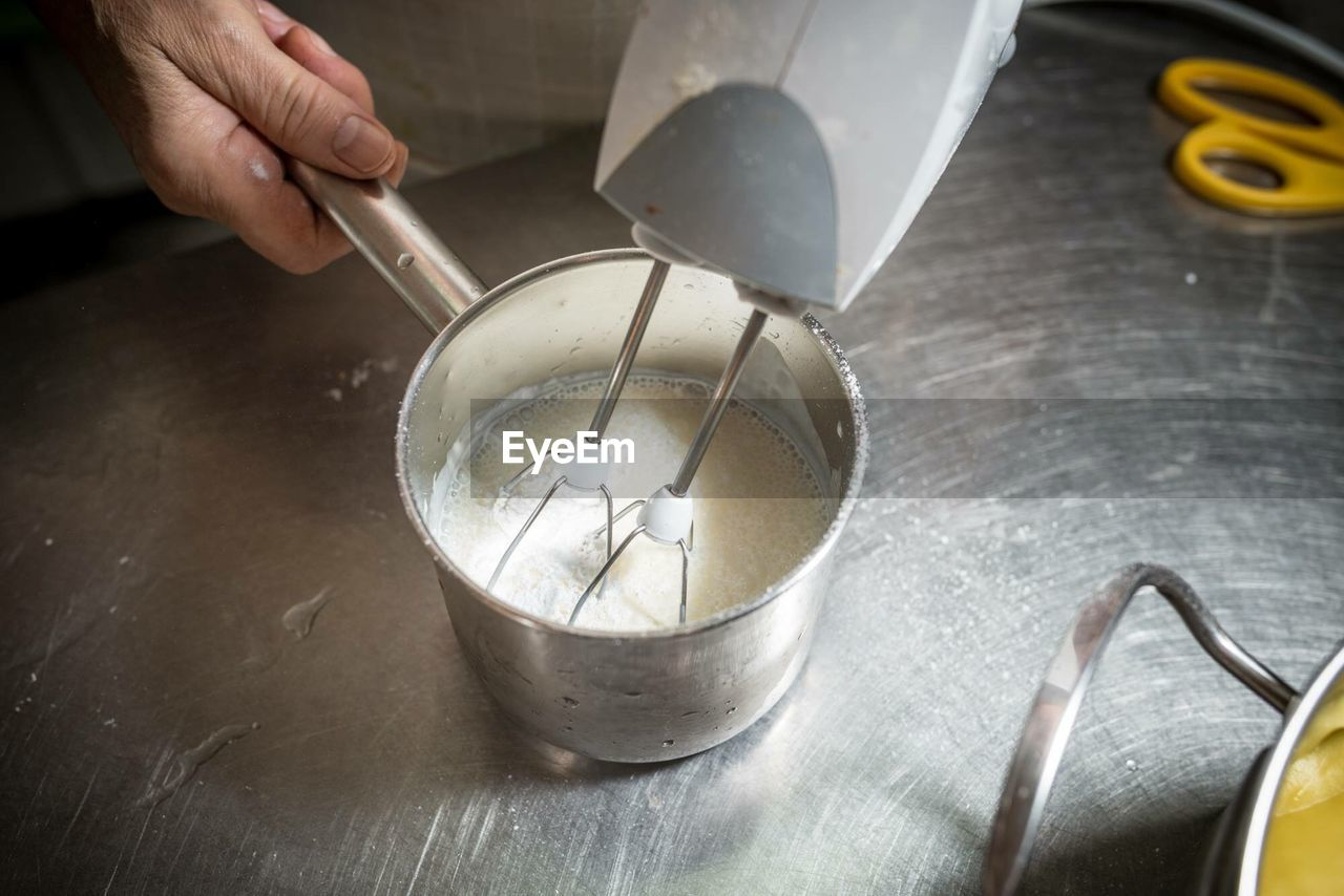 Cropped hand preparing food with wire whisk in kitchen