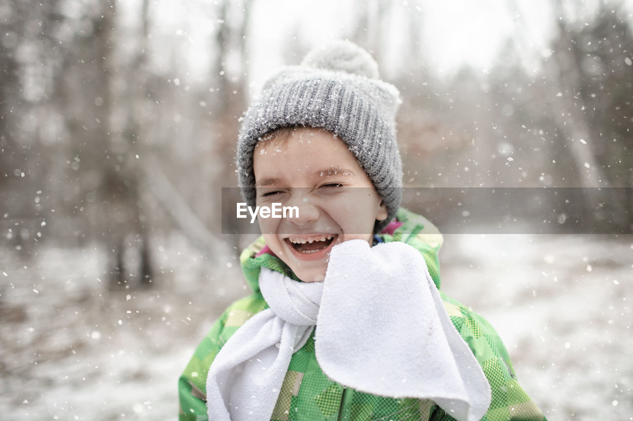 Portrait of laughing boy standing outdoors during winter