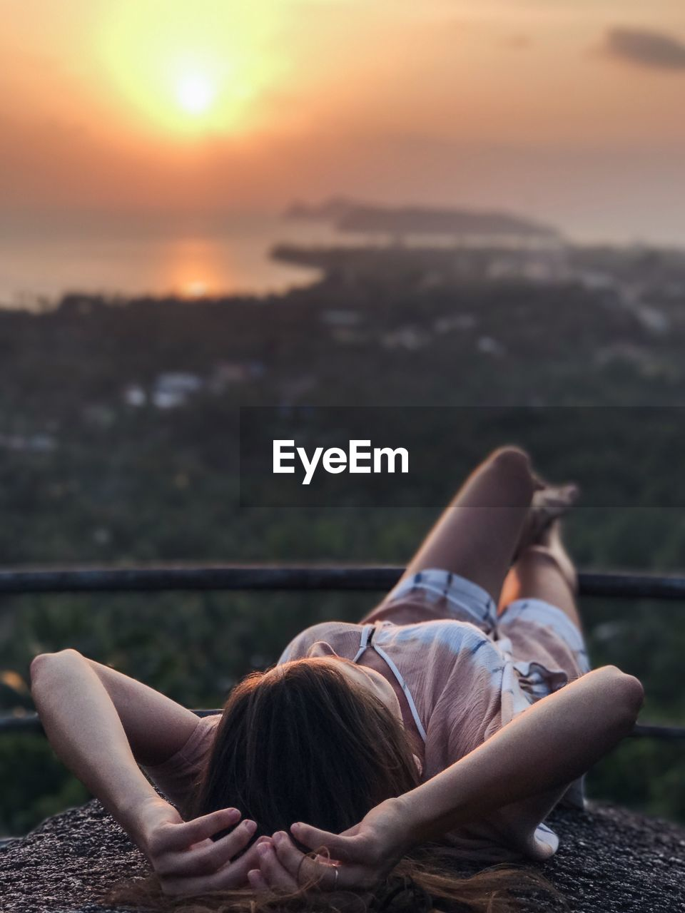 Woman Lying Down Outdoors At Sunset