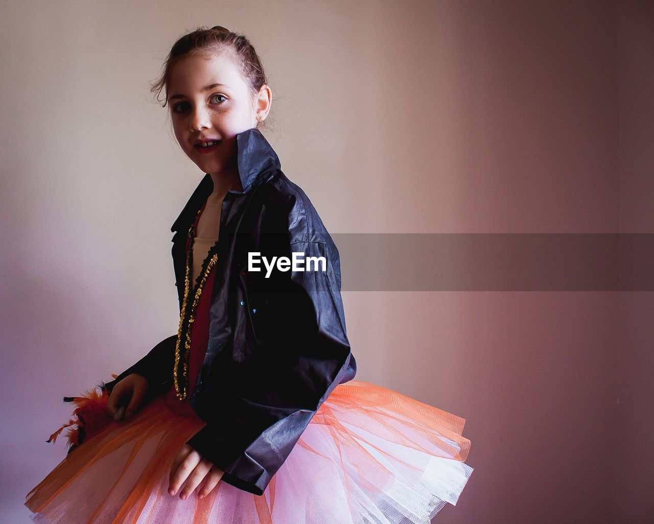 Side View Of Confident Girl Wearing Tutu And Jacket Against Wall