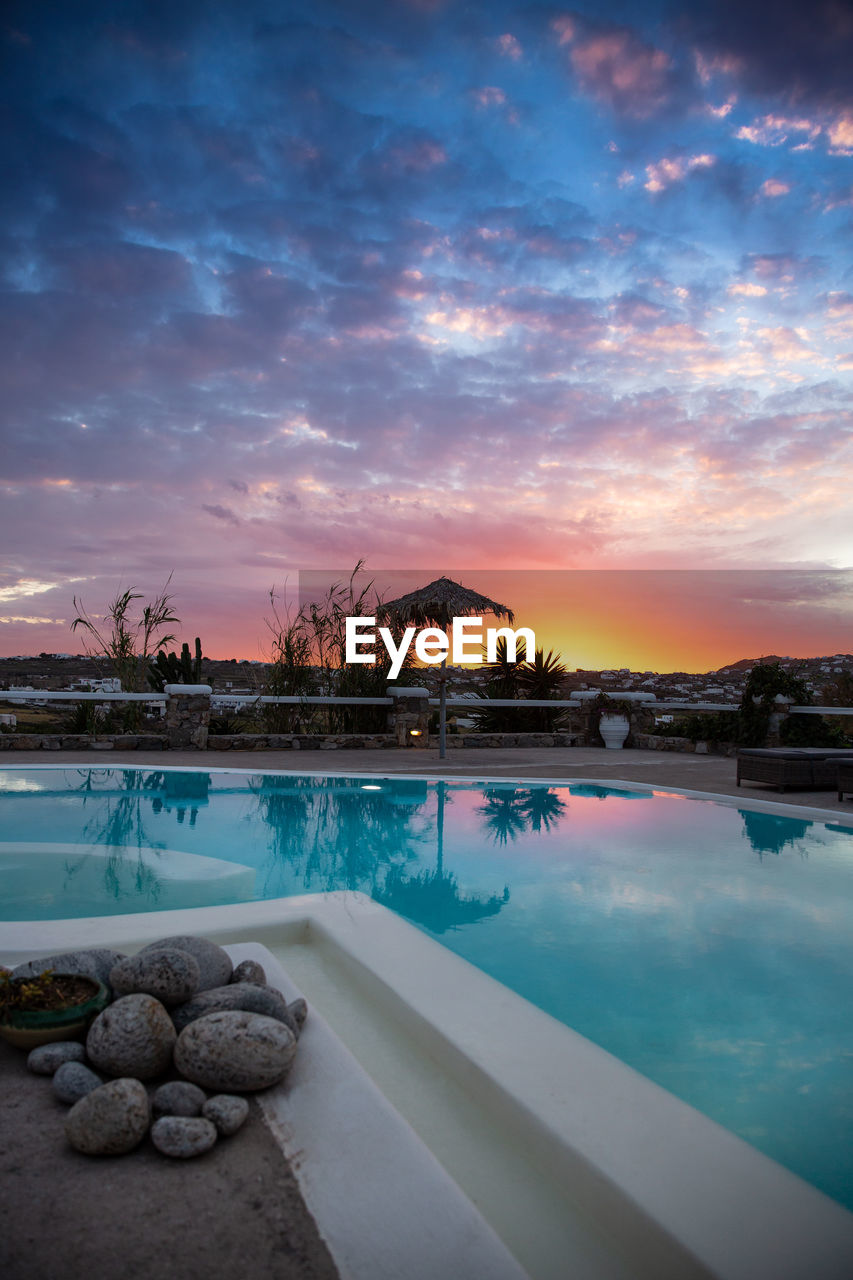 VIEW OF SWIMMING POOL AGAINST SKY AT SUNSET