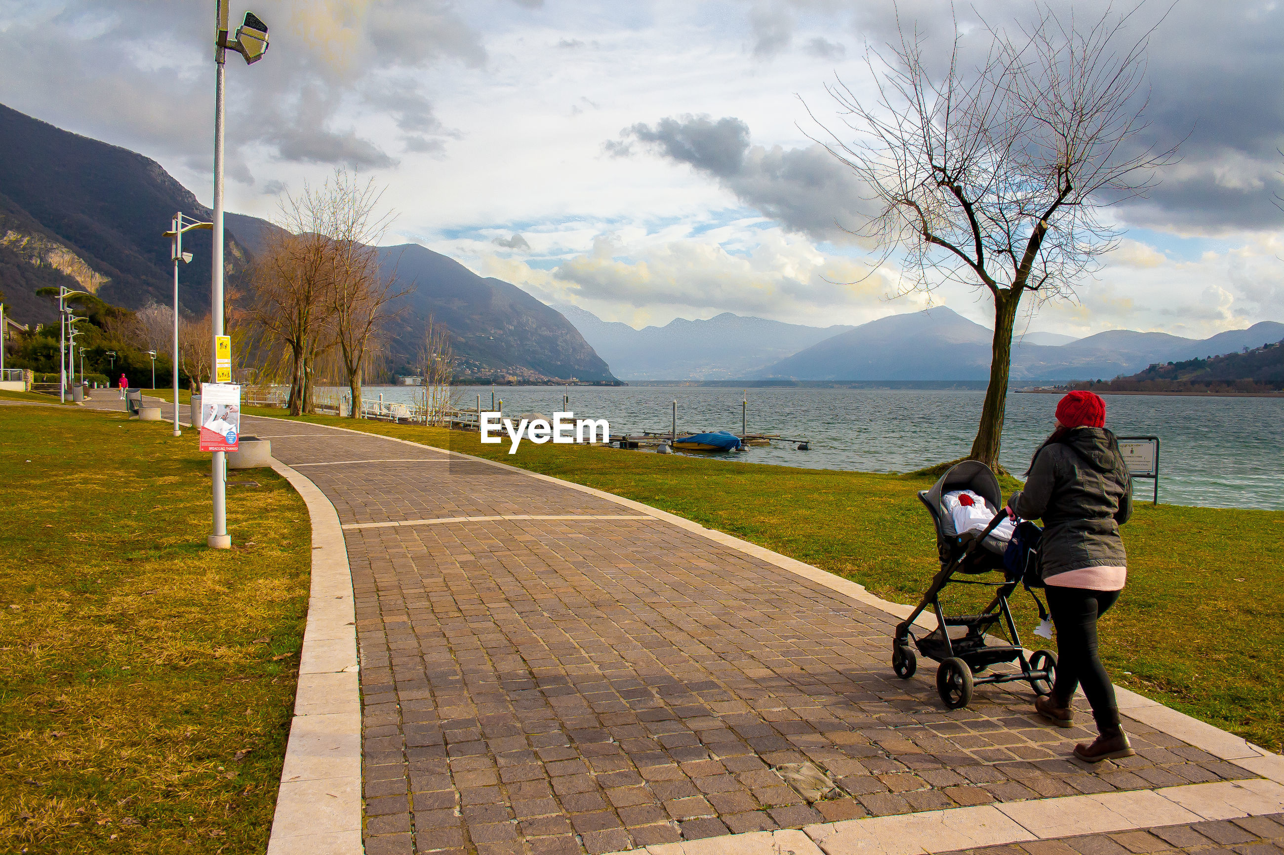 Rear view full length of woman pushing baby carriage by lake on footpath