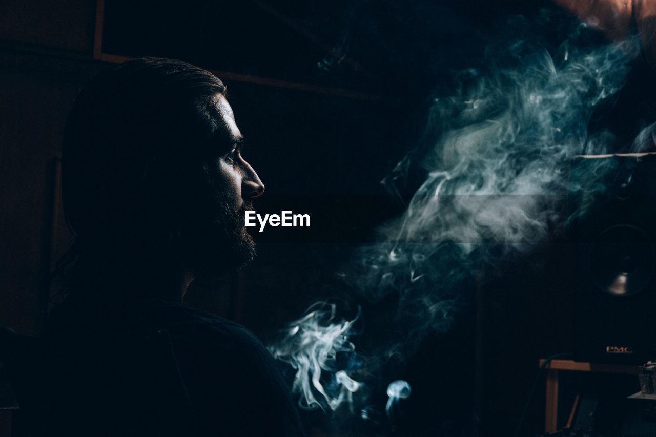 Man Looking At Smoke In Darkroom