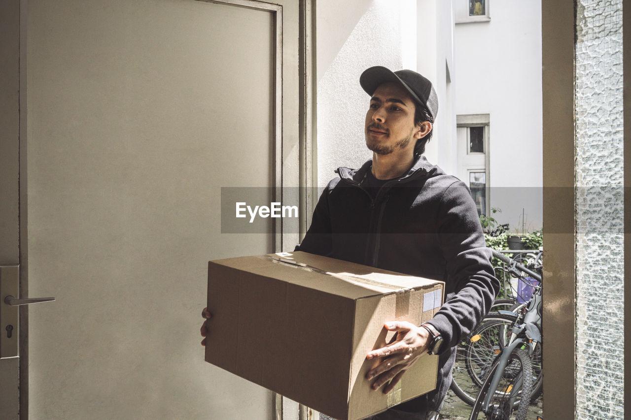YOUNG MAN WEARING HAT STANDING AGAINST DOOR OF BUILDING