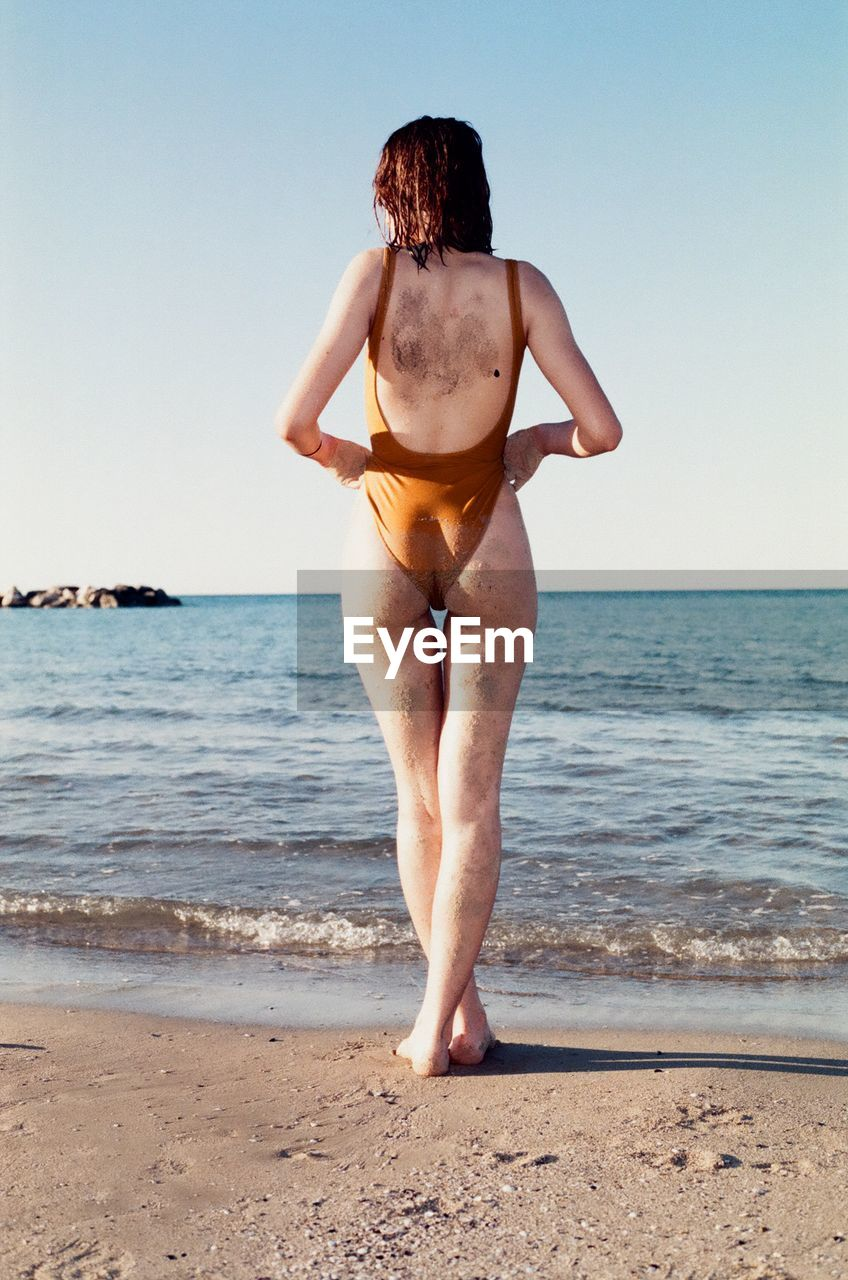 Rear view of woman in swimsuit standing on beach against clear sky