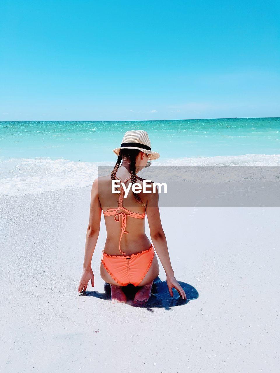 Rear View Of Teenage Girl Wearing Bikini Kneeling At Beach Against Sky During Sunny Day
